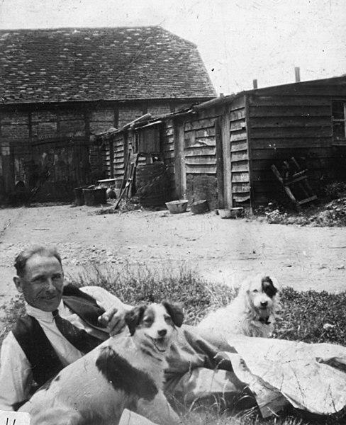 <font size=3><u> - Birmingham Yard Scene - </u></font> (BS0195)  Ernest Townsend outside the wash-houses and John West's workshop with the Field's dog Jack.  Behind him is Patch, Alice Lane's dog.