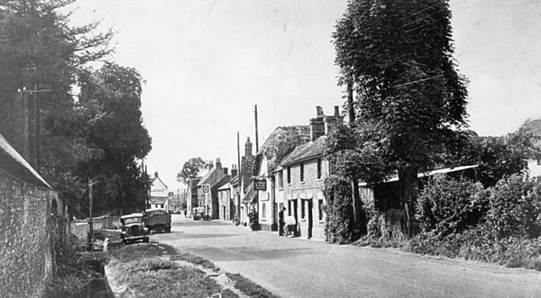 <font size=3><u> - Brook Street - </u></font> (BS0065)  Very early shot of Brook Street. Mr Cherrill's farm on the left. The barn on the left is corner of Old Barn Close?  Cars denote between wars.   Pub is the Lamb and Flag first, then the Farmer's man.