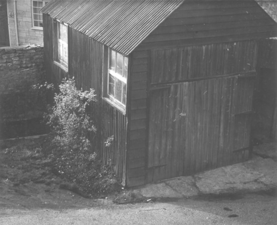 <font size=3><u> - Garage at 4 Brook Street - </u></font> (BS1119)  One of those puzzles.  The Brook Street building shown in this picture, recently handed in to the archive, was dismantled in 1980.  It was replaced by the garage at the end of No. 4 Brook Street, still there today, in 2007.  Part of No.6 Brook Street - built in the 1950s - is just visible in the top corner.   It is alleged to have been bus garage, but whose bus, and is there anyone who can tell us about it?