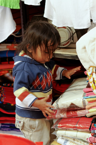 little boy stacking goods at a shop. Quito Ecuador