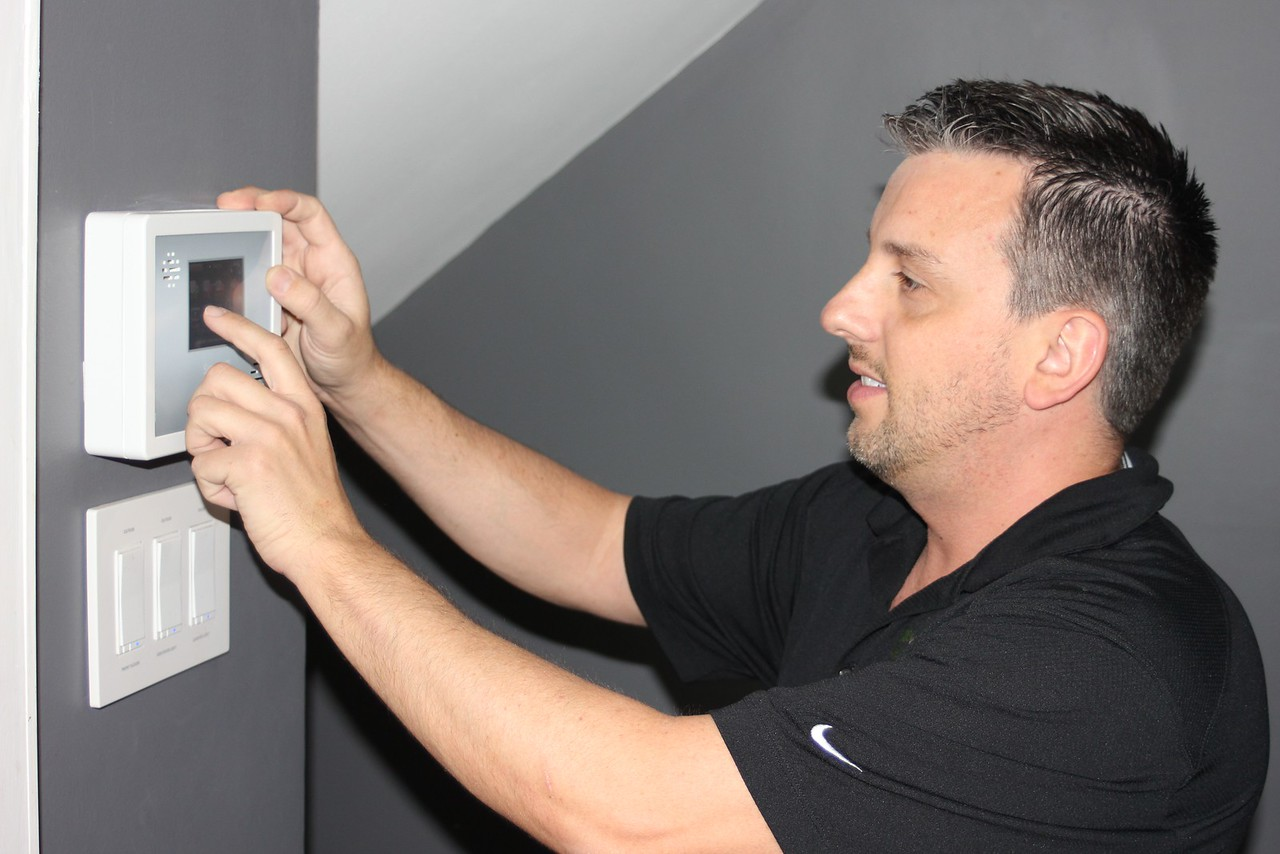 """Wesley Kasperski of Allen Park, President and CEO of WESCOMM Technologies, shows a security system control panel similar to one he installed last June at 4055 Fullerton, in the Russell Woods neighborhood of Detroit, to protect the Detroit Land Bank home during renovation while it was featured on """"This Old House"""" season 37, episode 18, Detroit / Ready for Rehab. WESCOMM also installed security systems on other Detroit Land Bank houses under construction. Sue Suchyta – For The News-Herald"""