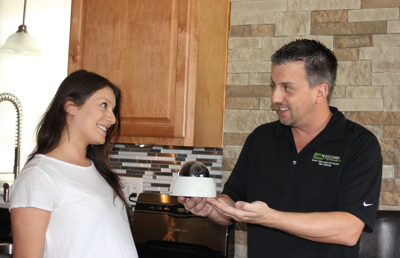 """Wesley Kasperski (right) of Allen Park, President and CEO of WESCOMM Technologies, shows a security system dome camera to Zena Toma, Director of Sales. The local security company installed a security system last June at 4055 Fullerton, in the Russell Woods neighborhood of Detroit, to protect the Detroit Land Bank house during renovation while it was featured on """"This Old House"""" season 37, episode 18, Detroit / Ready for Rehab. WESCOMM also installed security systems on other Detroit Land Bank houses under construction. Sue Suchyta – For The News-Herald"""