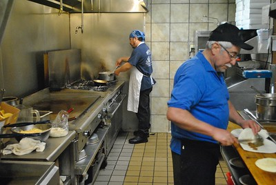 Pancho's owner Jose Longoria (right) and his nephew Julio Beccera work together in the kitchen at Pancho's Lincoln Park location. Robert Kobylasz – For The News-Herald