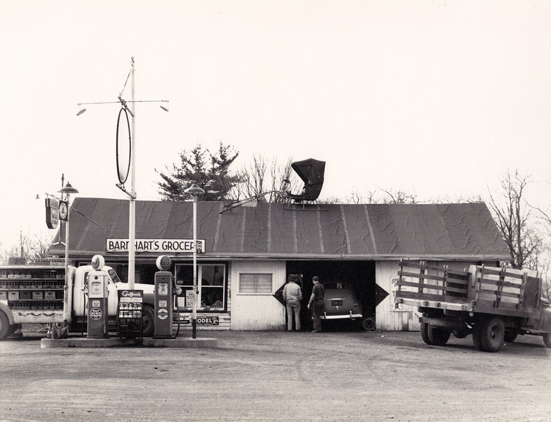 Mike and Thelma Barnhart's Grocery and Garage taken around 1951 on the corner of Rt. 90 and 34 in Genoa.  They had bought the garage from Ralph Manzari in 1945.  Thelma had a grovery store in the south end and husband Mike maintained a two bay garage at the other end.  (Photo ID: 30489)