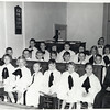 Alberta Huff and the Genoa Church choir.  Front row: Jean Edwards, Cheryl Valentine, Debbie Jones, Crystal Coon, Darlene Sellen, Mary Jane Nettleton, Lynn Hargett, Alberta Huff.  Second row: Syndey Thrasher, Alan Conklin, David Valentine, Elliot Lauterdale, Alfred Enzian, Bruce Jones, Bill Steams. Third row: ?, Margaret Ecker, Susan Enzian, Roberta Leanard, Margaret Able, Frances Nettleton, Frances Wood. Fourth row: Merit Murray. (Photo ID: 30472)