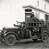 1920 Fire Truck with wooden spoke's and rubber tire's.  Main Street, Genoa, South side.  The fire house with it's bell in the back. (Photo ID: 27960)