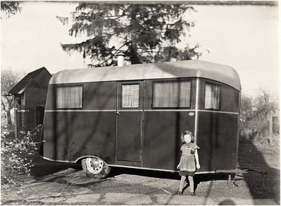 Rosie (Robinson) Shields standing next to Glen Robinson's trailer. Glen was a station agent when he was away from home. His family could come and stay with him. (Photo ID: 28067)