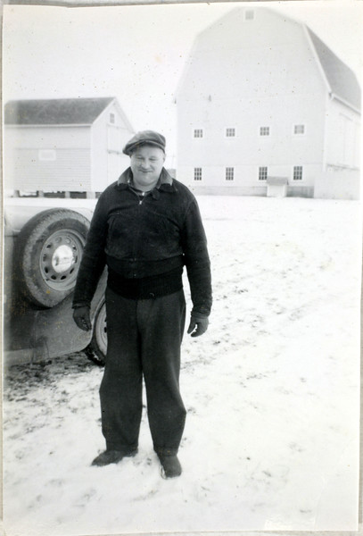 """Dirty"" Jim Ryan, cousin of Jo Parmenter. In the back are Mahaney barns. (Photo ID: 35741)"