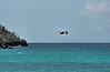 Brown pelican flying out over Gardner Bay.<br /> <br /> Gardner Bay, Isla Espanola,<br /> Galapagos Islands.