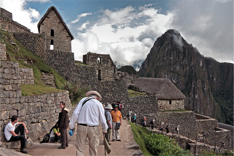 """Machu Picchu #04<br /> <br /> Huayna Picchu Mountain anchors one end of the narrow ridge upon which the site called Machu Picchu was built. Machu Picchu Mountain is at the other end of the ridge.  Both mountains were considered sacred by the Incas.  Huayna Picchu lies at what modern visitors would consider the far end of the site, and it stands on the far right of this picture, taken shortly after entering the site.<br /> <br /> Most tourists, especially those such as our group who are only """"day trippers"""", enter the site by crossing the main section of agricultural terraces about midway between top (where the main entrance for the Incas lies) and the bottom.  The terraces begin on the far side of the row of building immediately in front of us.<br /> <br /> (This is a slight re-edit of the version of this picture in the 'South American Sampler' gallery.)<br /> <br /> (Mapped)"""