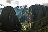 D136-2009  Notice the road and buildings at the base of the peak to the left of the river.<br /> <br /> Original caption:  Machu Picchu #02<br /> <br /> A glimpse of the Rio Urubamba winding far below.  The isolated 'sugar loaf' peak on the left is called Putucusi, 'Happy Peak' (also spelled Putukusi).  Along with Mt.s Machu Picchu and Huayna Picchu, it was considered a sacred peak, an apu.  A recently discovered portion of the Inca Trail scales the peak.  From its summit one has spectacular views of Machu Picchu and the surrounding mountains.<br /> <br /> Machu Picchu, Peru<br /> Taken May 16, 2009; edited 2014