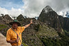 D136-2009  Our guide, in this shot, is gesturing toward the Eastern Urban sector of the Machu Picchu archaeological site.  Huayna Picchu lies beyond, just right of center.  <br /> Original caption:  Machu Picchu #18<br /> <br /> Our wonderful guide, Edwin Torres.  His facial features bespeak significant Inca blood in his ethnic heritage.<br /> <br /> Machu Picchu, Peru<br /> Taken May 16, 2009; edited 2014