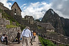 "D136-2009  (latitude -13.16491717056400; longitude -72.54495620727500)<br /> Original caption:  Machu Picchu #04<br /> <br /> Huayna Picchu Mountain anchors one end of the narrow ridge upon which the site called Machu Picchu was built. Machu Picchu Mountain is at the other end of the ridge.  Both mountains were considered sacred by the Incas.  Huayna Picchu lies at what modern visitors would consider the far end of the site, and it stands on the far right of this picture, taken shortly after entering the site.<br /> <br /> Most tourists, especially those such as our group who are only ""day trippers"", enter the site by crossing the main section of agricultural terraces about midway between top (where the main entrance for the Incas lies) and the bottom.  The terraces begin on the far side of the row of building immediately in front of us.<br /> <br /> Machu Picchu, Peru<br /> Taken May 16, 2009; edited 2014"
