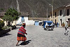 An Indian woman, very possibly Quechua, the ethnic group related to the Incas, in traditional dress, complete even to the footwear.  She seems to be carrying fresh flowers in her basket/hat.  Often I saw people in native dress, but wearing modern western athletic shoes.  Also in the shot is one of the Andean tricycle taxis, emblazoned on the back with the anachronistic Batman logo.