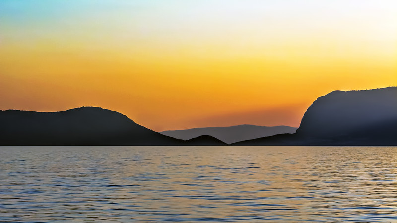 Stark coastal hills against a pastel background of sky and sea.  Turkey