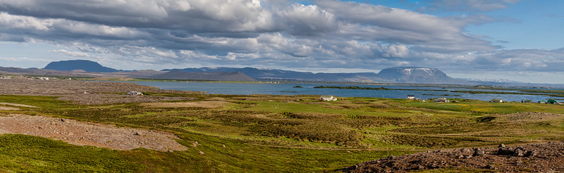 Panorama of Lake Mývatn taken looking eastward from the west side.  On the far shore, slightly left of center, is the volcanic crater Hverfjall.  Also on the far shore, to the right of center, is the mountain Bláfjall, which actually sits to the south of the lake and is much farther away than Hverfjall.  It just seems to be about the same distance away because it is so much larger.  On the near shore are some farms and private residences.<br /> <br /> Stitched from three handheld singles, each with the following exposure settings:  RAW, neutral, ISO 160, f/9.0, 1/400 sec, 45 mm.<br /> <br /> June 20, 2010; approximate 7:12 pm or 19:12 GMT.  Sunset for this longest day but one was approximately 0:45 am, I seem to recall.<br /> (I've made a guess of our location at the time and map tagged it.)<br /> Mývatn, Iceland