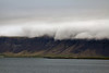 View from Reykjavík harbor.  Low clouds mask the tops of distant mountains.