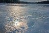 Iridescence in thin clouds is reflected in ice and melt water on the lake.<br /> <br /> December 27, 2008<br /> Crooked Lake