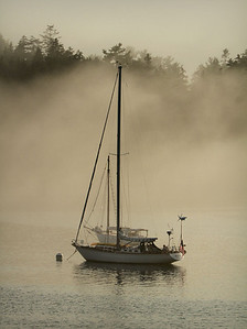 Fog rolls in from a distance behind this anchored sail boat.