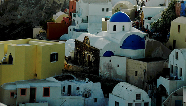 Santorini - Town of Oia<br /> The town of Oia is perched at the summit of the caldera, on the northern tip of the island.  This picturesque fishing village was devastated by an earthquake in 1956 and has been completely rebuilt.  Oia is comprised of 2 streets.  Buildings and tree trunks are painted white every year and stand out against the backdrop of rust color layers of rock, earth and volcanic ash.