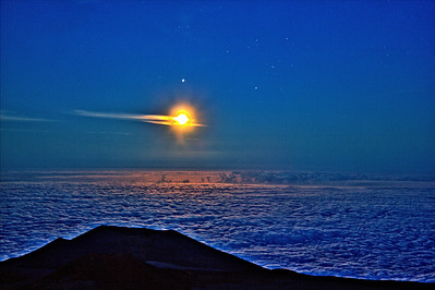 The full moon is high above the clouds as seen from the Keck Observatory on Hawaii's Mauna Kea