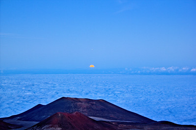 Keck Observatory on Hawaii's Big Island atop Mauna Kea - taken just just as the full moon rises above the clouds.  The small illuminated spot just above the moon is Jupiter.