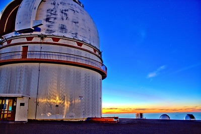 Keck Observatory on Hawaii's Big Island atop Mauna Kea - taken just just as the full moon rises and sun has eased beneath the clouds. The moon is providing an orange reflection of off the metal structure.