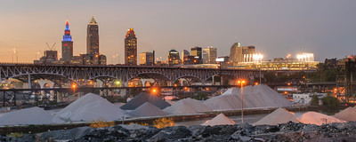 The skyline of the City of Cleveland along with a lit up Progressive Field taken from the Tremont neighborhood in Cleveland, Ohio. The Innerbelt Bridge and the industrial valley are in the foreground.