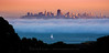A lone sailboat sails toward the fog drifting into San Francisco Bay as the city skyline is illuminated by the setting sun.