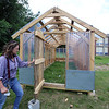Locke Middle School industrial arts teacher Teresa Rogers, with the greenhouse that students have almost finished building behind the school. (SUN/Julia Malakie)