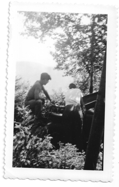 A scene of the Jeep climbing Mount Moosilauke on September 9, 1951, with Roger Gilmore working on the engine, and Bobby Moody watching.