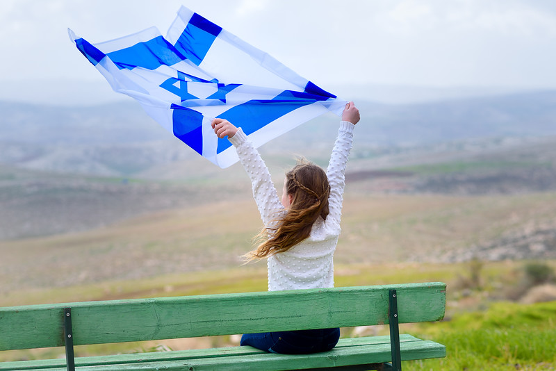 Israeli jewish little girl with Israel flag back view.
