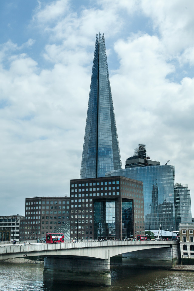 London Buses crossing London Bridge in front of the Shard in London, England