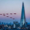 Fly past at sunset  of the Royal Air Force Red Arrows Aerobatic team by The Shard and Guy's Hospital with London Docklands in the distance.