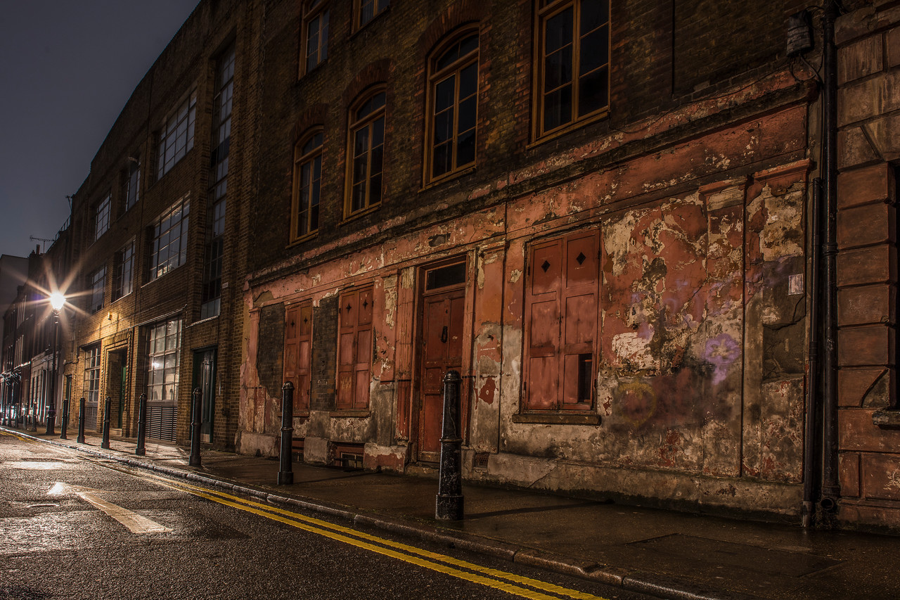 Night image in the rain of a dilapidated wall in a back street in East London near Brick Lane
