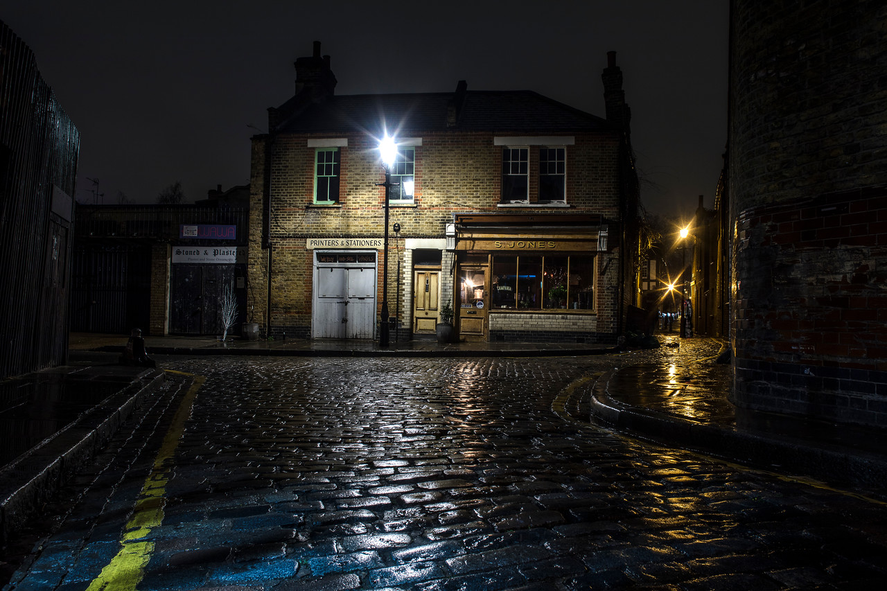 Old Victorian London at night with reflections on cobbled streets