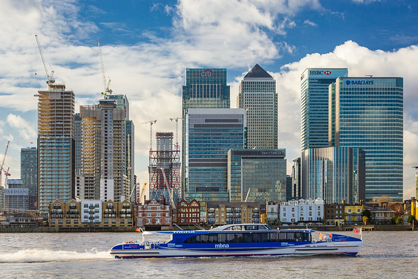 MBNA high speed catamaran on Thames heading past modern skyscrapers of Canary Wharf, January 2018, Greenwich London