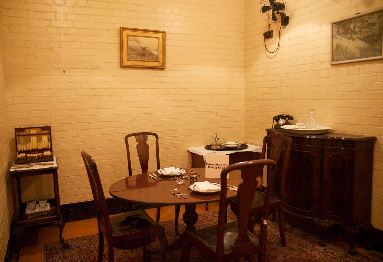 """Churchill War Rooms Museum Churchill's Dining Room <br><br> The Churchill War Rooms is a fascinating museum in London, consisting of the Cabinet War Rooms and the Churchill Museum. The war rooms are an underground complex that housed the British government during World War II. During the war, the rooms were in constant use by officers responsible for producing daily information for the King, Prime Minister, and the military Chiefs of Staff.  <br><br> The Cabinet War Rooms are located in the Treasury Building in the Whitehall area of Westminster not far from the Parliament Buildings. They became operational in August 1939, days before the German invasion of Poland, and remained in operation until August 1945. <br><br> The War Rooms were fortified on several occasions during the German bombing of London. However, a recurring theme of the museum was that it was not all that secure. A sign on the wall of the museum reads:  <br><br> This was the Global Hub of Information on the War <br><br> The Government's Secret Bomb Shelter <br><br> An East Target that was Never Hit <br><br> The rooms were preserved after the war. A limited number of people could tour the rooms until they were opened to the public in 1984. The museum was reopened in 2005 following a redevelopment as the Churchill Museum and Cabinet War Rooms, now simply called the Churchill War Rooms.   <br><br> See the<a href=""""http://www.iwm.org.uk/visits/churchill-war-rooms"""">Churchill War Rooms website</a> for more detail."""
