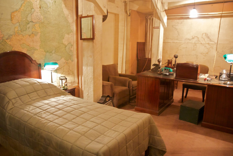 """Churchill War Rooms Museum Churchill's Office and Bed <br><br> Churchill made four wartime broadcasts from the Cabinet War Rooms. His office also had a bed, but he rarely slept there, preferring 10 Downing Street. <br><br> The Churchill War Rooms is a fascinating museum in London, consisting of the Cabinet War Rooms and the Churchill Museum. The war rooms are an underground complex that housed the British government during World War II. During the war, the rooms were in constant use by officers responsible for producing daily information for the King, Prime Minister, and the military Chiefs of Staff.  <br><br> The Cabinet War Rooms are located in the Treasury Building in the Whitehall area of Westminster not far from the Parliament Buildings. They became operational in August 1939, days before the German invasion of Poland, and remained in operation until August 1945. <br><br> The War Rooms were fortified on several occasions during the German bombing of London. However, a recurring theme of the museum was that it was not all that secure. A sign on the wall of the museum reads:  <br><br> This was the Global Hub of Information on the War <br><br> The Government's Secret Bomb Shelter <br><br> An East Target that was Never Hit <br><br> The rooms were preserved after the war. A limited number of people could tour the rooms until they were opened to the public in 1984. The museum was reopened in 2005 following a redevelopment as the Churchill Museum and Cabinet War Rooms, now simply called the Churchill War Rooms.   <br><br> See the<a href=""""http://www.iwm.org.uk/visits/churchill-war-rooms"""">Churchill War Rooms website</a> for more detail."""