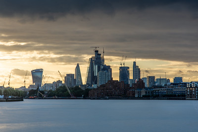 Sunset behind the City of London skyline on the River Thames