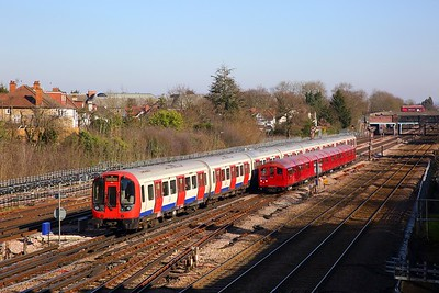 Train 746 composed of 4 cars 1938 tube stock working 1311 Moorgate to Ealing Common via Amersham approaching Harrow on the Hill with S stock 21091 overtaking it on the 24th February 2019 1