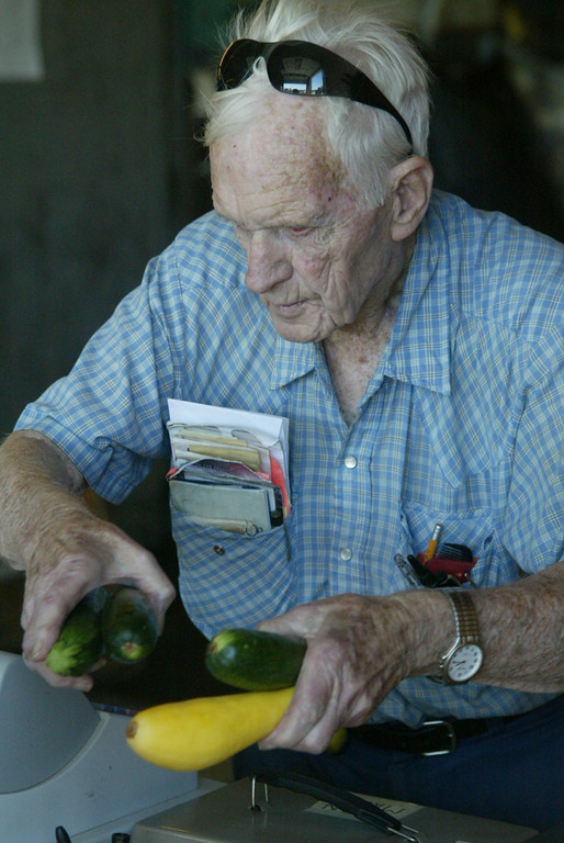 Mr. Elwood at Elwood Farm in 2007 ringing up produce; squash, in the farmstand.