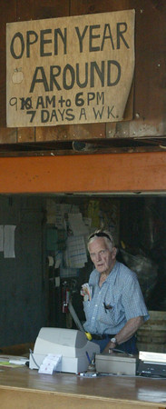 Wayland Elwood in 2007 in the Elwood Farmstand with a hours sign over his head he is behind the counter