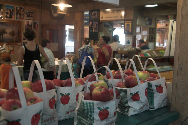 Apple bags full in the foreground with a farmstand checkout line of customers at Mack's in Londonderry, New Hampshire