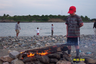Campfire and Scouts (a couple skipping rocks across the water) on the beach with Fort Warren (on Georges Island) in the background.