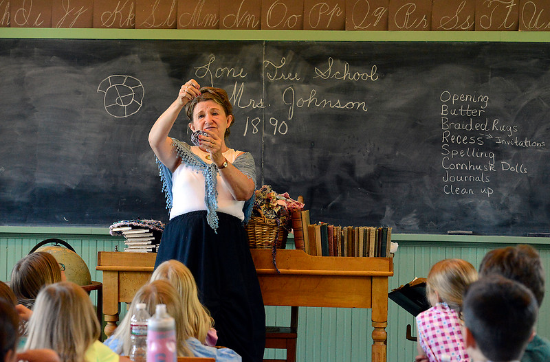 Teri Johnson shows students how to make a rag rug Wednesday, June 15, 2016, at the Lone Tree Schoolhouse at North Lake Park in Loveland. Students participate in activities that are like a typical school day in 1890 during the summer session classes in the one-room schoolhouse. (Photo by Jenny Sparks/Loveland Reporter-Herald)