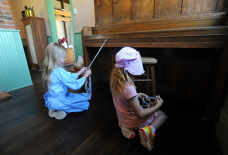 Leighanne Gibbons, 7, left, and Kathryn Cox, 7, braid rags while making a rag rug Wednesday, June 15, 2016, at the Lone Tree Schoolhouse at North Lake Park in Loveland. Students participate in activities that are like a typical school day in 1890 during the summer session classes in the one-room schoolhouse. (Photo by Jenny Sparks/Loveland Reporter-Herald)