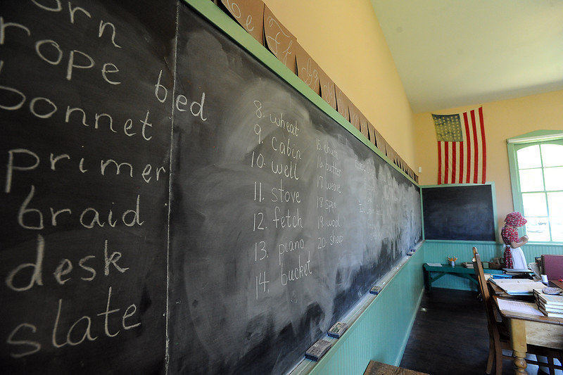 Spelling words fill the blackboard as Ellory Anne Bauersfeld, right, gets a pair of scissors Wednesday, June 15, 2016, at the Lone Tree Schoolhouse at North Lake Park in Loveland. Students participate in activities that are like a typical school day in 1890 during the summer session classes in the one-room schoolhouse. (Photo by Jenny Sparks/Loveland Reporter-Herald)