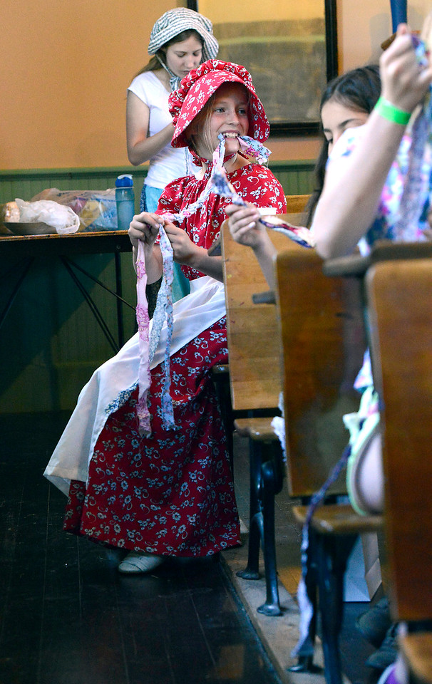 Sporting a bonnet and long dress, Ellory Anne Bauersfeld, 8, braids rags while making a rag rug Wednesday, June 15, 2016, at the Lone Tree Schoolhouse at North Lake Park in Loveland. Students participate in activities that are like a typical school day in 1890 during the summer session classes in the one-room schoolhouse. (Photo by Jenny Sparks/Loveland Reporter-Herald)