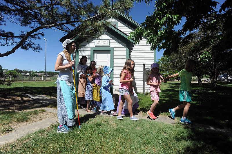 Teacher's helper Sarah Lee, 16, left, waits for children to head to recess Wednesday, June 15, 2016, at the Lone Tree Schoolhouse at North Lake Park in Loveland. Students participate in activities that are like a typical school day in 1890 during the summer session classes in the one-room schoolhouse. (Photo by Jenny Sparks/Loveland Reporter-Herald)